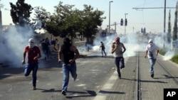 Người Palestine chạy tránh hơi cay khi họ đụng độ với lực lượng an ninh Israel trong đám tang của Mohammed Abu Khudair ở Jerusalem, thứ Sáu, 4/7/2014.