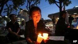 Một người phụ nữ thắp nến cầu nguyện cho hòa bình trên bán đảo Triều Tiên bên ngoài Đại sứ quán Mỹ ở Seoul hôm 31/8.