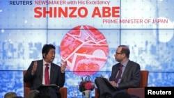 아베 신조(왼쪽) 일본 총리가 21일 미국 뉴욕에서 진행된 로이터통신 초청 간담회에서 국제 현안에 대해 발언하고 있다.