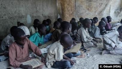 Almajirai in Maiduguri read scriptures from the Quran on wooden slates.