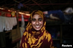 Formin Akter smiles as she poses for a picture before heading to Chittagong to attend school at the Asian University for Women, in Cox's Bazar, Bangladesh, Aug. 24, 2018.