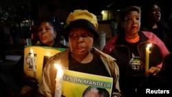 Des Sud-Africains devant l'ancienne maison de Nelson Mandela à Soweto