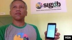 "Mohammad Ismail menunjukkan aplikasi ""Signteraktif"" (Foto: VOA/Nurhadi)."