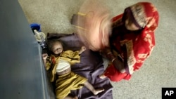 Indian mother fans her child with her sari as the child awaits treatment for diarrhea at a government-run children's hospital in Allahabad, India, June 25, 2009.