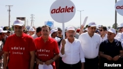 "FILE - Turkey's main opposition Republican People's Party (CHP) leader Kemal Kilicdaroglu (C) and Secretay-General of the Socialist International Luis Ayala (2nd L) walk flanked by supporters during the 14th day of a protest dubbed ""justice march"" against the detention of CHP's lawmaker Enis Berberoglu, in Duzce, June 28, 2017. The placard reads ""Justice."""