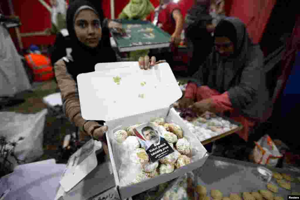 6일 이집트 거리에서 무르시 전 대통령을 지지하는 주민이 과자 상자 안에 들어있는 무르시의 사진을 보이고 있다.