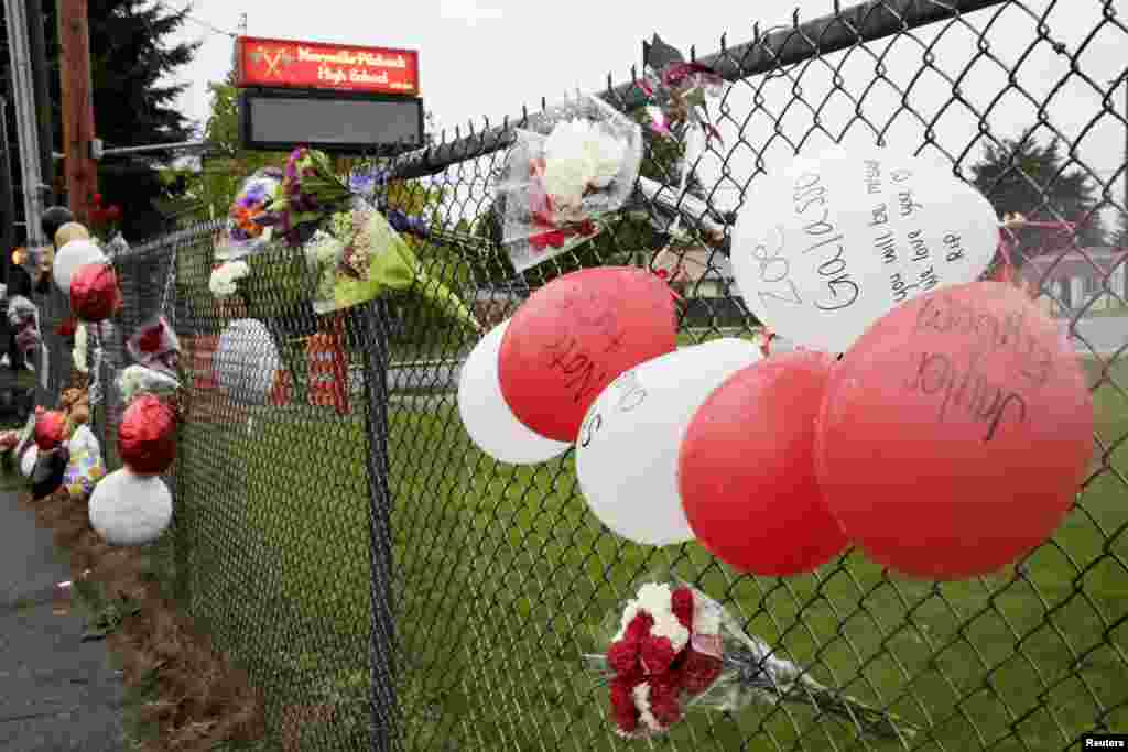 Balloons and flowers are tied to a fence outside of Marysville-Pilchuck High School as a memorial to the victims of a school shooting in Marysville, Washington, Oct. 25, 2014.