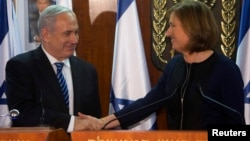 Israel's Prime Minister Benjamin Netanyahu (L) shakes hands with former Foreign Minister Tzipi Livni, head of the centrist Hatenuah party, during their joint statement at the Knesset, the Israeli parliament, in Jerusalem, February 19, 2013.