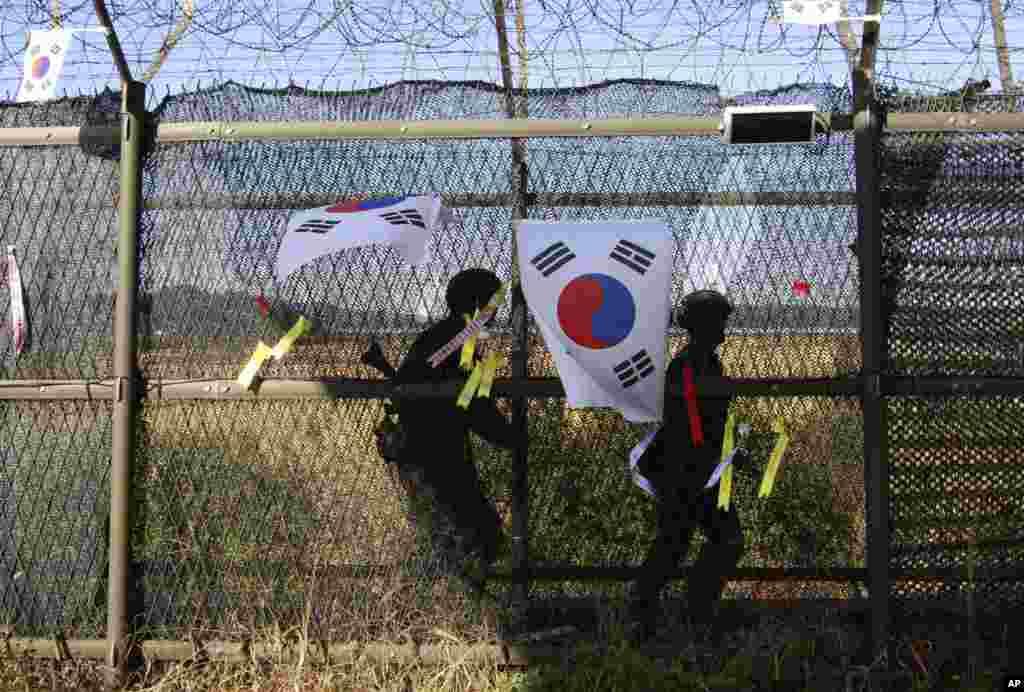 15일 판문점 인근 비무장지대 남측지역에서 순찰 중이던 한국 군인들이 철책에 태극기를 달고 있다.
