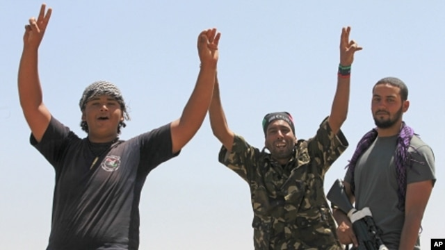 Libyan rebel fighters celebrate as they drive into the coastal city of Zawiyah, August 15, 2011.