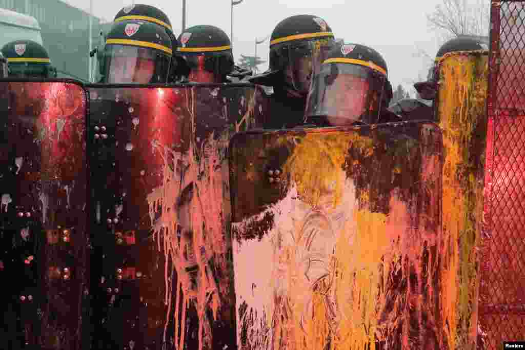 French CRS riot police are covered with paint during clashes with demonstrators in front of tire-maker Goodyear Dunlop's France headquarters in Rueil Malmaison, near Paris.
