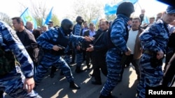 FILE - Members of the Russian Interior Ministry security forces attempt to block the way for Crimean Tatars to cross a checkpoint connecting Crimea and Ukraine's Kherson region to meet with Tatar leader Mustafa Dzhemilev, near Armyansk May 3, 2014.