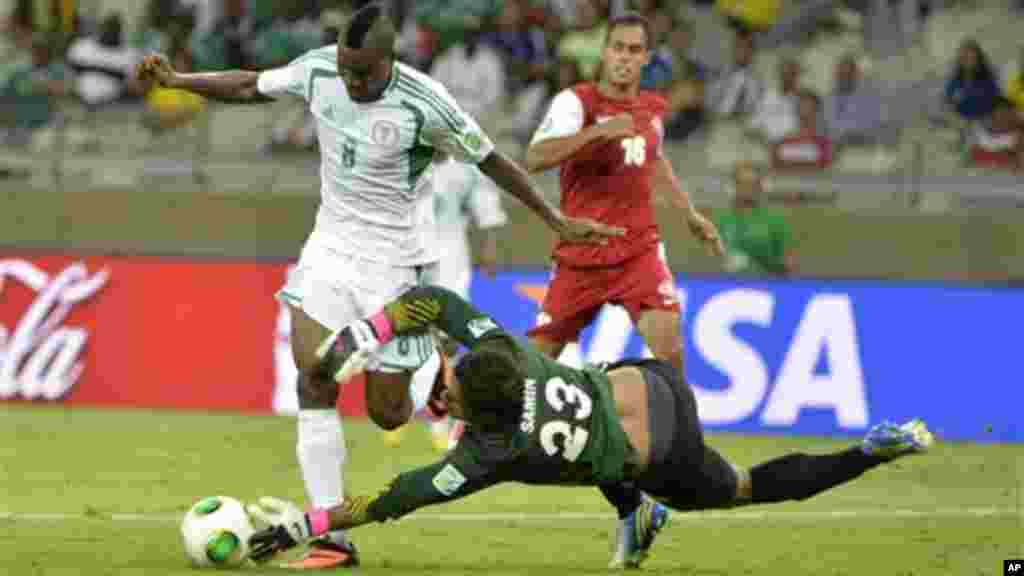 Nigeria's Brown Ideye is stopped by Tahiti goalkeeper Xavier Samin, right, during the Confederations Cup match between Tahiti and Nigeria.