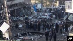 伊拉克安全部队在巴格达的卡拉达社区查看一枚汽车炸弹炸出的弹坑