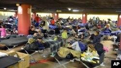 Des réfugiés se reposent dans une aire de stationnement de la gare principale de Salzbourg en Autriche, le dimanche 13 septembre 2015.