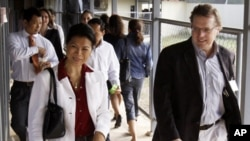 Seng Theary, left, walk through a gate at the U.N.-backed tribunal court hall.