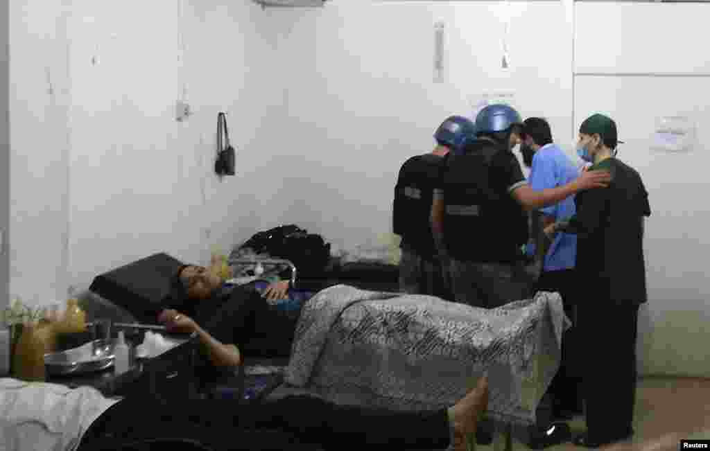 U.N. chemical weapons experts visit a hospital where wounded people affected by a suspected gas attack are being treated, in a southwestern Damascus suburb, August 26, 2013.