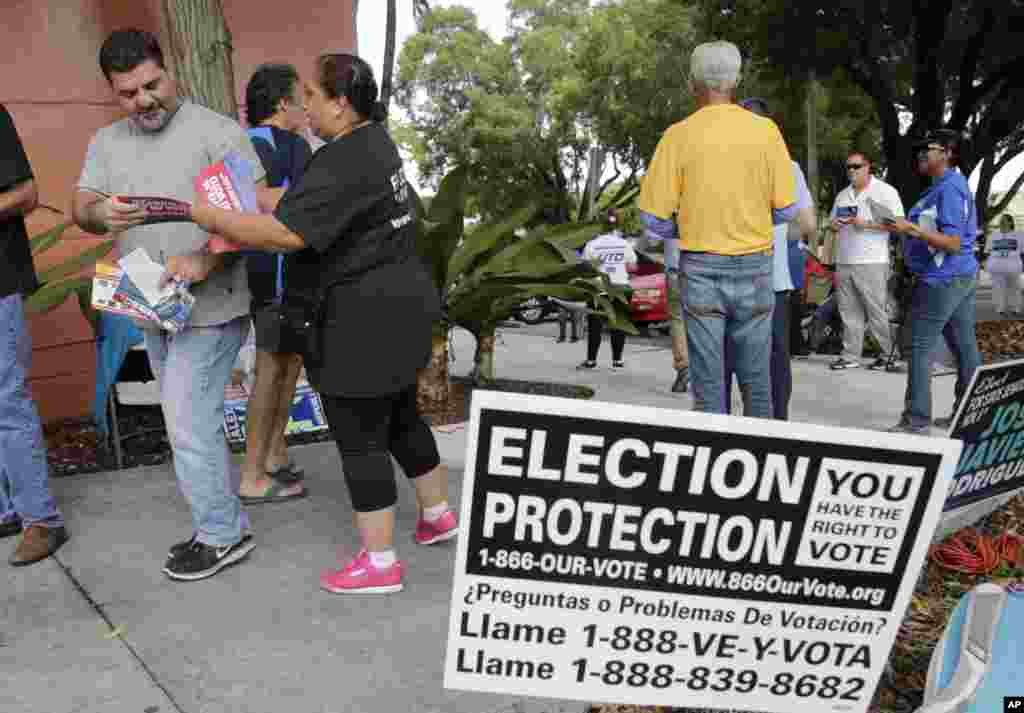 Ingrid Vaca, of Falls Church, Virginia, a volunteer with Election Protection, second from left, hands a voter a leaflet informing him about voter's rights, outside of a polling station at the Miami-Dade County Auditorium, in Miami, Florida.