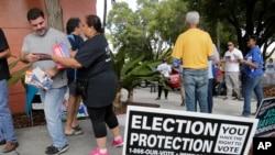 Ingrid Vaca, de Falls Church, en Virginie, bénévole de protection électorale, deuxième à partir de la gauche, remet à un électeur une brochure sur les droits des votants, à l'extérieur d'un bureau de vote à l'auditorium du comté de Miami-Dade, à Miami, 8