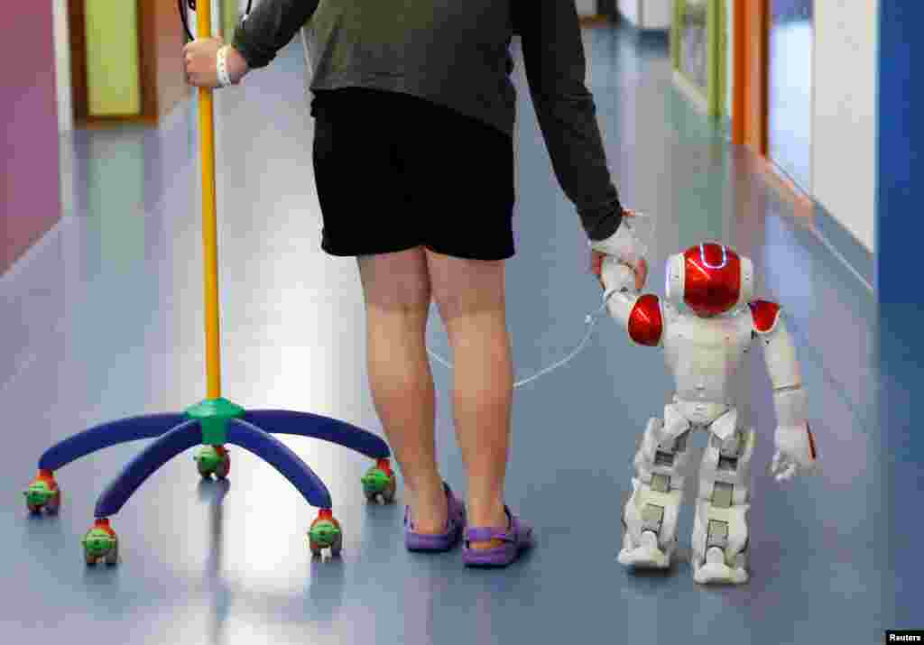 Belgian Ian Frejean, 11, walks with, Zora the robot, a humanoid robot designed to entertain patients and to support care providers, at AZ Damiaan hospital in Ostend, Belgium.