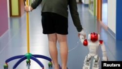 "Belgian Ian Frejean, 11, walks with ""Zora"" the robot, a humanoid robot designed to entertain patients and to support care providers, at AZ Damiaan hospital in Ostend, Belgium June 16, 2016."