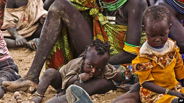 In Kenya, Turkana women and their children wait to receive relief food supplies near the Kakuma Refugee Camp, northwest of Kenya's capital Nairobi, August 8, 2011