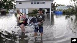 Một gia đình ở thành phố Slidell, tiểu bang Louisiana rời căn nhà đã bị ngập lụt sau khi bão isaac thổi qua