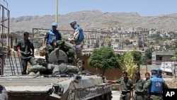 United Nations (U.N.) observers examine a Syrian army tank during a field visit to the al-Zabadani area, near Damascus, May 6, 2012. Al-Zabadani is one of the locations where protests against the regime of Syrian President Bashar al-Assad were being held.