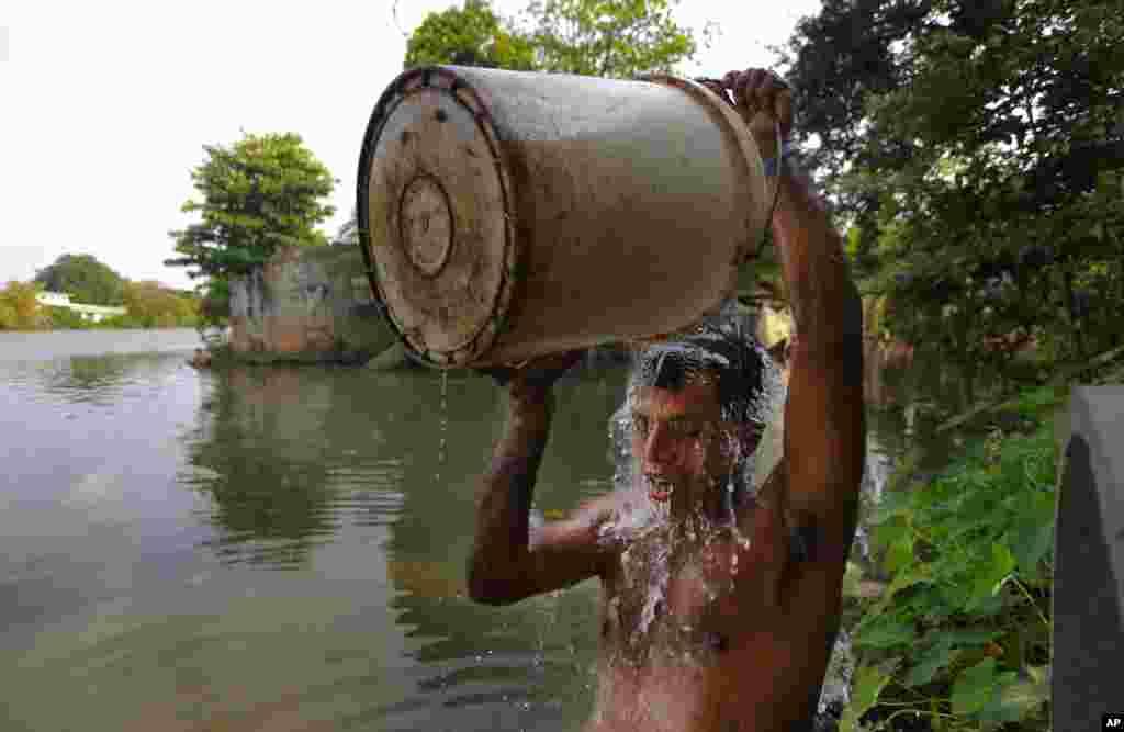 د بېوزلۍ په نړیواله ورځ، یو سریلانکایي نارینه چې د یوه کانال په ککړو اوبو ځان وینځي.