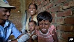 Foriza Begum, di belakang, pengungsi Rohingya Muslim yang baru tiba dari Myanmar, bereaksi ketika melihat anak perempuannya, Nosmin Fatima, menangis saat disuntik vaksin campak dan rubela di pusat kesehatan di Teknaf, Bangladesh, 2 Oktober 2017.