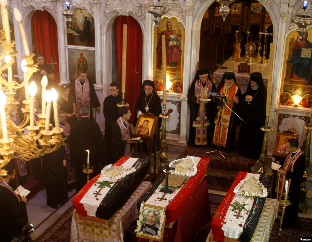 Clerics and other people attend the funeral of three men at Catholic Patriarchate in Damascus, Syria, on September 10, 2013.