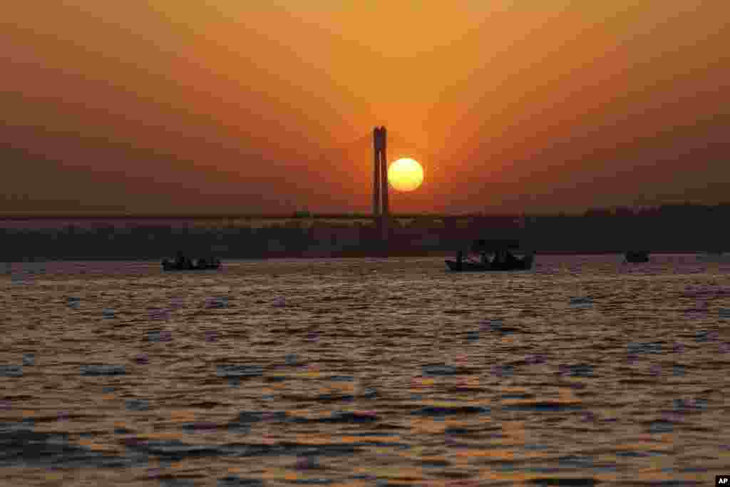 Tourists take a boat ride on the river Ganges at sunset in Allahabad, India.