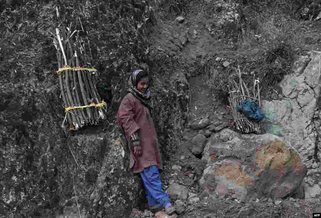 Seorang perempuan Muslim Kashmir beristirahat setelah mengumpulkan kayu bakar di Srinagar, Kashmir-India.