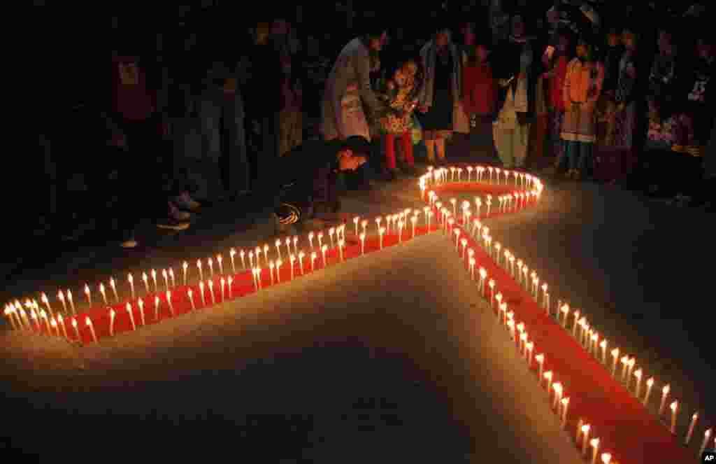 """An Népal, des femmes et des enfants de """"Maiti Nepal"""", un centre de réadaptation pour les victimes de trafic sexuel, ont allumé des bougies à la veille de la Journée mondiale du sida à Katmandou, 30 novembre 2015."""