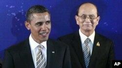 ປະທານາທິບໍດີມຽນມາ ທ່ານເທນ ເຊນ (Thein Sein) ຢືນຢູ່ທາງຫລັງ ປະທານາທິບໍດີສະຫະລັດ ທ່ານບາຣັກ ໂອບາມາ, ເວລາຖ່າຍຮູບໝູ່ ຢູ່ກອງປະຊຸມສຸດຍອດຂອງບັນດາປະເທດເອເຊຍຕາເວັນອອກ ທີ່ເກາະບາຫລີ ຂອງອິນໂດເນເຊຍ ໃນວັນເສົາ, ທີ 19, 2011 (AP Photo/Charles Dharap