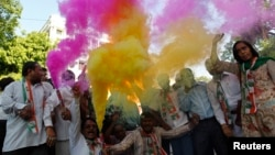 Supporters of India's ruling Congress party use color crackers during election celebrations outside party headquarters in Ahmedabad on May 8, 2013.