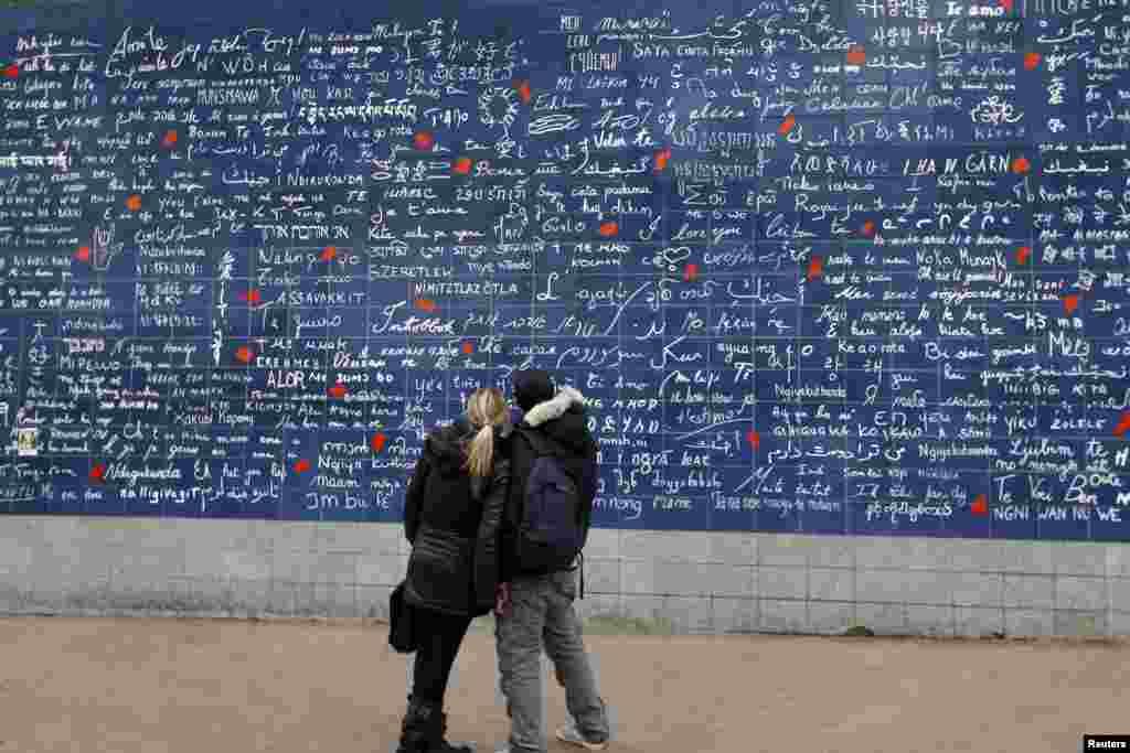 """Dvoje mladih Parižana, takođe zaljubljenjih, pred """"zidom ljubavi,"""" umjetničkom kreacijom Frederica Barona i Claire Kito."""