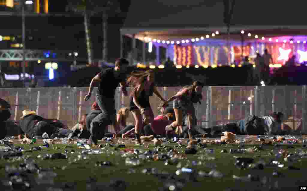 People run from the Route 91 Harvest country music festival after apparent gun fire was heard in Las Vegas, Nevada, Oct. 1, 2017. The gunman, identified as Stephen Paddock, 64, of Mesquite, Nevada, allegedly opened fire from a room on the 32nd floor of the Mandalay Bay Resort and Casino on the music festival, leaving at least 58 people dead and over 500 injured.