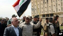 Iraqi Prime Minister Haider al-Abadi tours the city of Tikrit after declaring that it had been retaken from Islamic State militants by security forces, April 1, 2015.