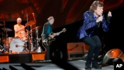 "Mick Jagger, right, performs with Keith Richards, center, and Charlie Watts on drums as The Rolling Stones play in their ""Zip Code"" tour in Pittsburgh, June 20, 2015."