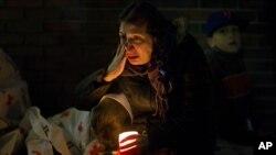 一名悼念者2012年12月16日在康涅狄克州纽敦举行的悼念枪击案死难者的烛光晚会上聆听奥巴马总统通过扩音器讲话的时候留下泪来