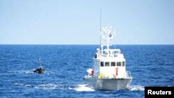 A Japanese coast guard patrol vessel tows a boat carrying nine people off the coast of Noto Peninsula, in northwestern Japan, Sept. 13, 2011. On Thursday, Japan returned to North Korea three crew members from a capsized fishing boat off the Noto Peninsula