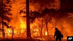 Seorang petugas pemadam kebakaran melewati rumah yang terbakar saat Dixie Fire berkobar di Plumas County, California, 24 Juli 2021. (AP Photo/Noah Berge)
