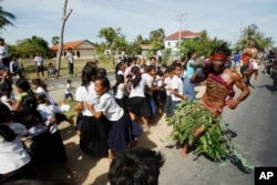 FILE - A local youth, front right, scares pupils on a street as he takes part in a ceremony to exorcize evil spirits and pray for rain amid the rice planting season at Pring Ka-ek village, northwest of Phnom Penh, Cambodia, May 22, 2015.