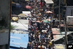 People crowd a street in a market on Lagos Island in Lagos, Nigeria, Oct. 11, 2011.