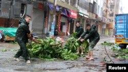 Người dân cố gắng loại bỏ một nhánh cây khỏi con đường khi bão Mujigae ập vào tỉnh Quảng Đông.