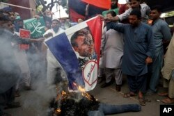 Supporters of Jamaat-e-Islami, a religious political party, burns a representation of a French flag with a defaced image of French President Emmanuel Macron during a protest.