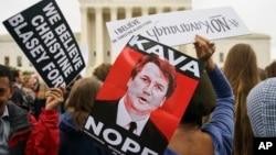 Des manifestants devant la Cour suprême tiennent des pancartes avec une image du juge Brett Kavanaugh à Washington, le 24 septembre 2018.