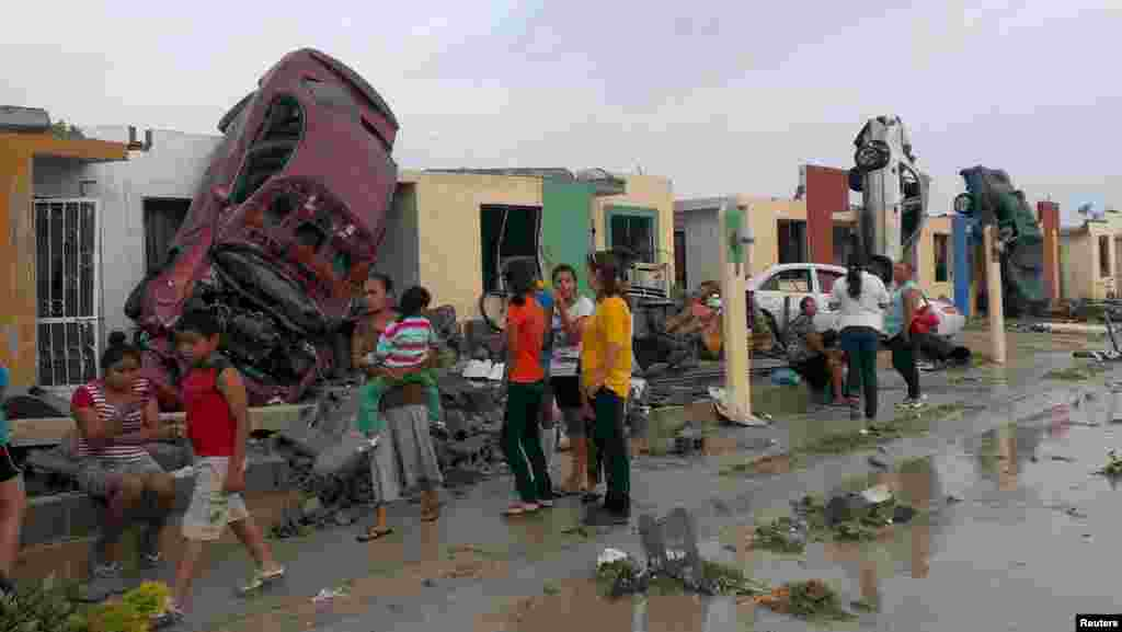 Residents stand outside their homes as damaged cars are seen after a tornado hit the town of Ciudad Acuna, state of Coahuila, Mexico.