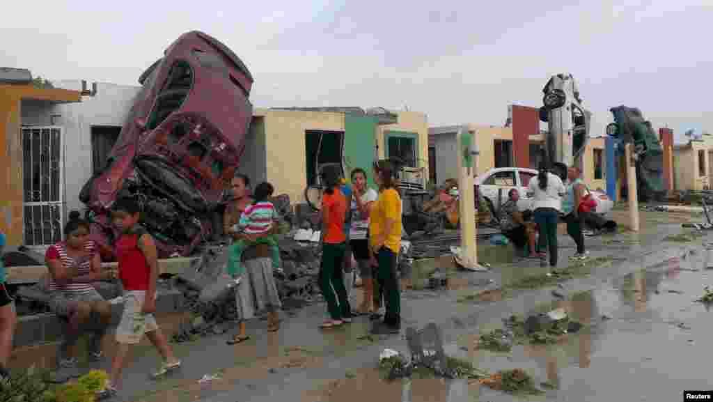 Người dân đứng bên ngoài nhà của mình với những chiếc xe hơi bị hư hại sau khi một cơn lốc xoáy quét qua thị trấn Ciudad Acuna, bang Coahuila, Mexico.